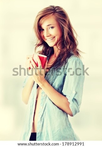 The beautiful young woman drinks morning coffee or tea  - stock photo