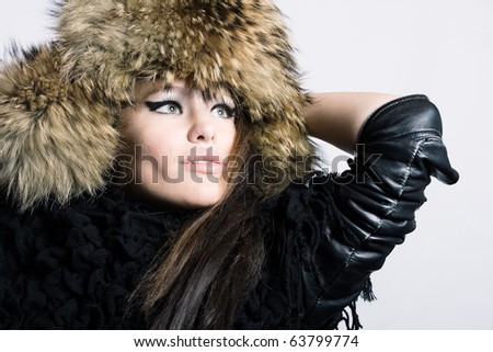 The beautiful young woman in a fur cap on a white background. - stock photo