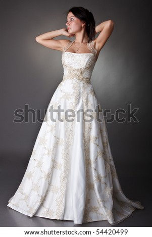 The beautiful young woman in a wedding dress on a grey background.