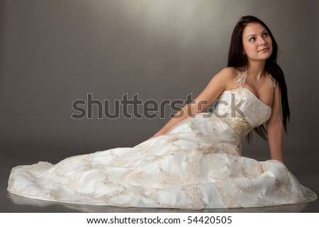 The beautiful young woman in a wedding dress on a grey background. - stock photo