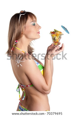 The beautiful young woman in bikini with fruit salad  and the drawn sun on a shoulder on a white background.