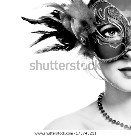 The beautiful young woman in mysterious venetian mask. Black and white photo - stock photo