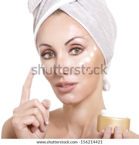 The beautiful young woman in towel with a cosmetic cream