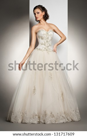 The beautiful young woman posing in a wedding dress over grey background - stock photo