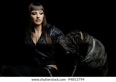 the beautiful  young woman sit with dog on black background