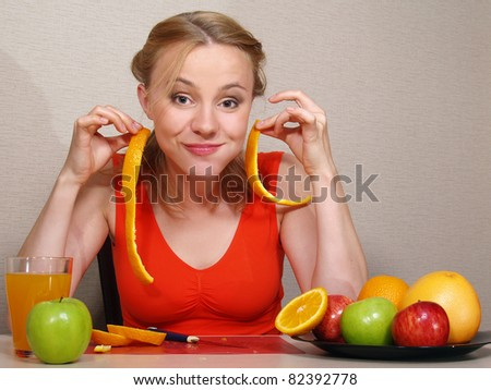 The beautiful young woman sits at a table and eats fruit