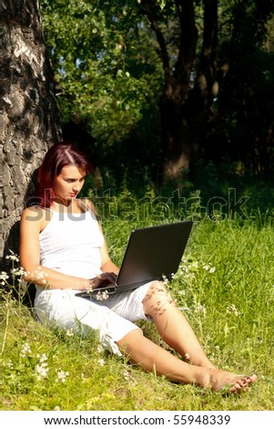 The beautiful young woman sits on a grass in a park with the laptop.