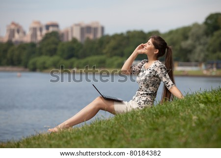 The beautiful young woman sits on a grass in the park with the laptop and mobile phone. - stock photo