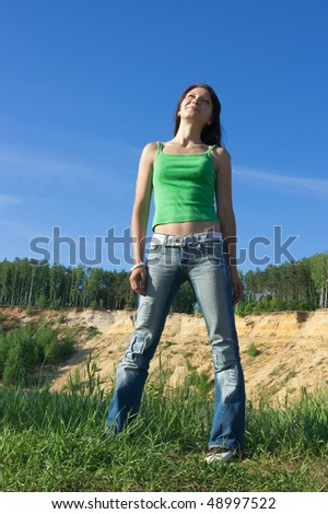 The beautiful young woman staying ashore and looking in the sky