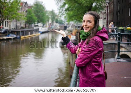 the beautiful young woman wearing a purple rain jacket shows us the beauty of Amsterdam someday Cloudy - stock photo