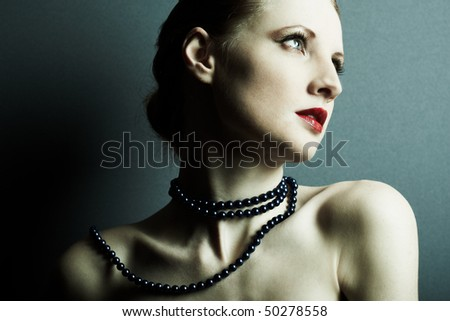The beautiful young woman with a dark blue beads on a neck - stock photo