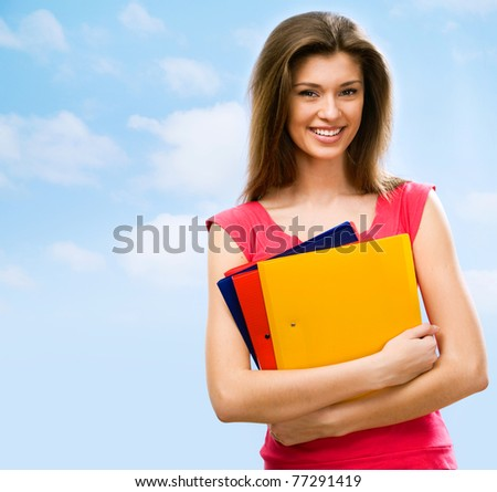 The beautiful young woman with color folders in hands - stock photo