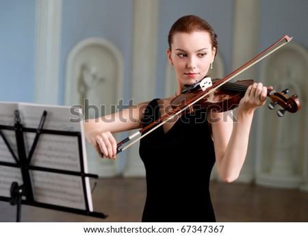 The beauty brunette plays the violin in concert hall - stock photo