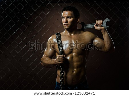 the beauty muscular worker  man,  with big wrench and  chain in hands, on netting fence background - stock photo