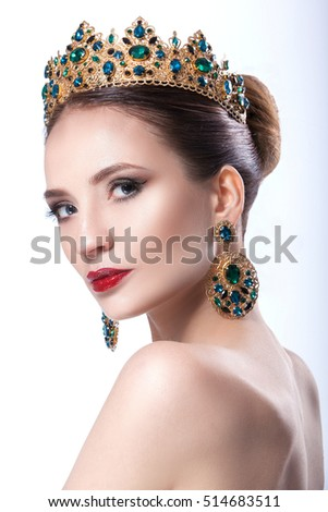 The beauty of a woman with a crown with a beautiful color makeup. red hair, straight hair, clear skin, beautiful face. Portrait shot in studio isolated on white background.