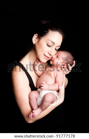 The beauty of motherhood, mother and cute baby. Parent holding infant with care and love, on black.