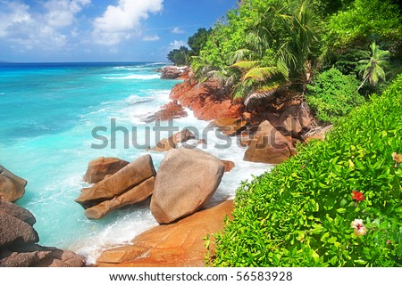 The Beauty Of The Seychelles, huge Boulders, Hibiscus and Palms fringe a stunning Beach on the idyllic island of La Dique - stock photo