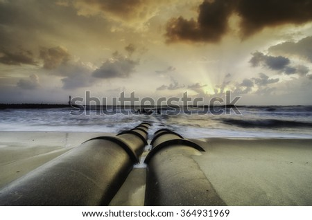 the beauty sunrise at the coastline. concrete drainage pipe at the beach. dark and dramatic clouds with ray of light - stock photo