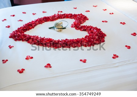 The bed topped with rose petal in heart shape and rose boutique inside, Decorate for couple in wedding day - stock photo