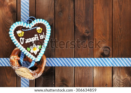 The beer is tapped - original bavarian salted soft pretzel and Oktoberfest gingerbread heart from Germany in front of wooden board - stock photo