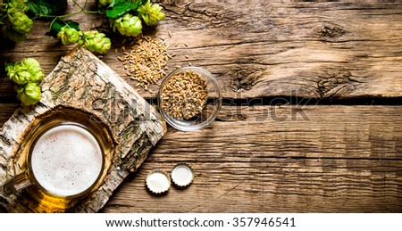 The beer style . Glass of beer on a birch stand, malt and hops on wooden background. Top view - stock photo
