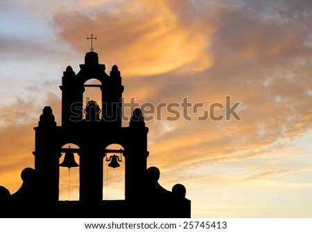 The bell tower of an authentic 1700's Spanish Mission in silhouette against a colorful sunset sky (Christian/Easter/Church image). - stock photo
