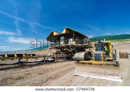the belt conveyor and bulldozer in opencast coal mine - Most - Czech Republic - stock photo