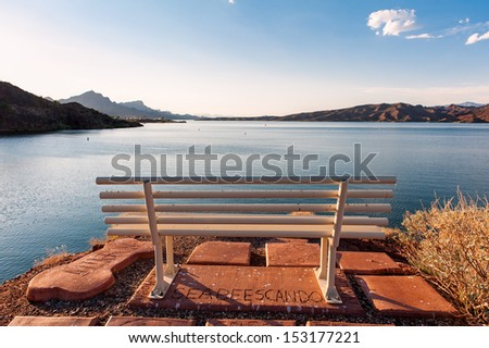 The bench in front of the lake under the blue sky - stock photo