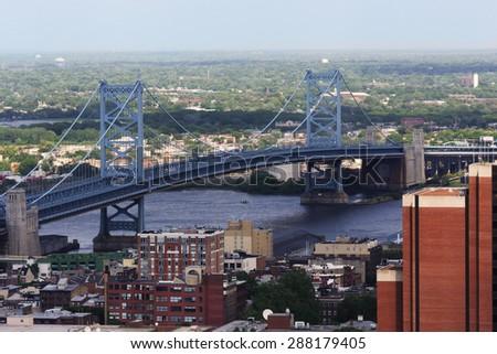 The Benjamin Franklin Bridge crosses the Delaware River connecting Philadelphia, Pennsylvania and Camden New Jersey.  The suspension bridge has been in service since 1926 - stock photo