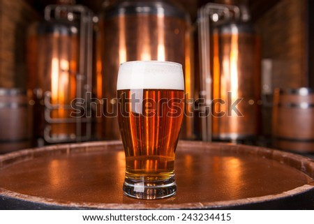 The best beer in town. Close-up of glass with fresh beer standing on the wooden barrel with metal container in the background - stock photo