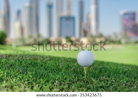The best day for golfing. Golf ball is on the tee for a golf ball on the grass on a golf course on the background of the city skyscrapers - stock photo