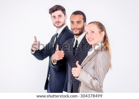 The best employees. Three confident and successful businessman standing in a row while businessman showing a thumbs up on a gray background