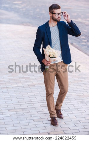 The best flowers for her. Full length of handsome young man in smart casual wear holding bouquet of flowers and adjusting his eyeglasses while walking by the street  - stock photo