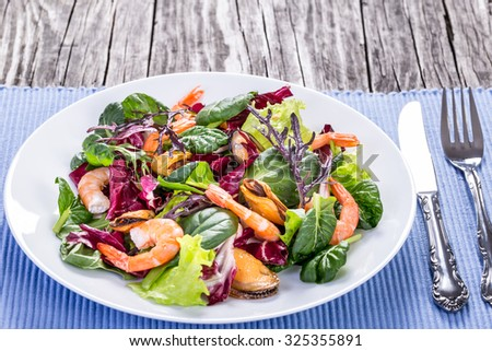 the best fresh salad of prawns, mussels and mixed lettuce leaves in the white dish on the old wooden table, rustic style, selective focus, macro, close-up  - stock photo