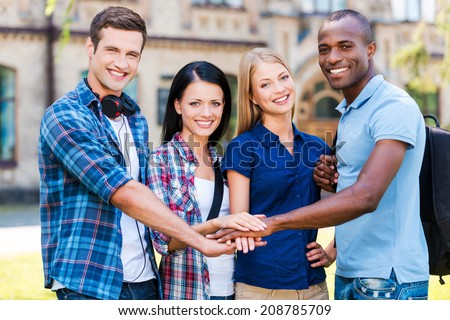 The best friends ever. Four happy young people holding their hands together and smiling while standing outdoors - stock photo