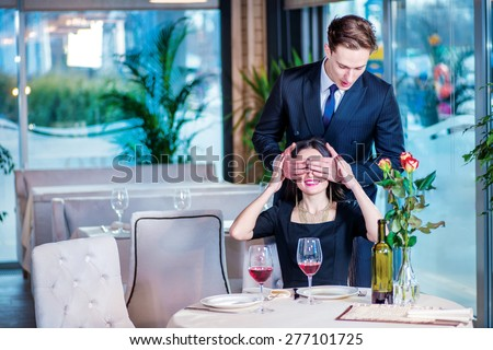 The best gift and evening. Romantic dinner in the restaurant. Young couple sitting at a table in the restaurant until the guy closed the girl her eyes with his hands - stock photo