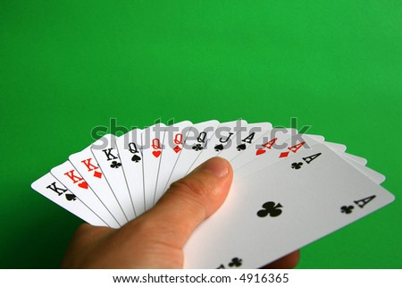 the best of cards in bridge...  It's incredible!  playing bridge - one hand (A,K,Q,J spades, A,K,Q hearts, A,K,Q diamonds, A,K,Q clubs)  background green, - stock photo
