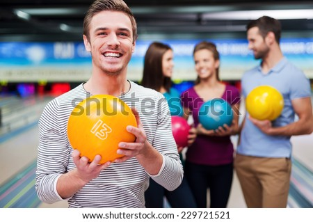 The best player. Handsome young men holding a bowling ball while three people communicating against bowling alleys  - stock photo