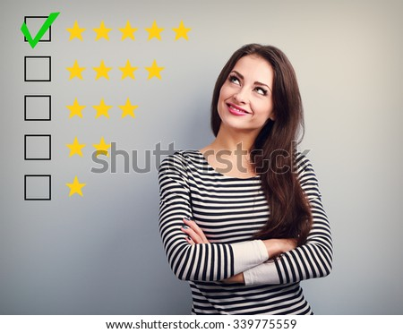 The best rating, evaluation. Business confident happy woman voting to five yellow star to increase ranking. On grey background - stock photo