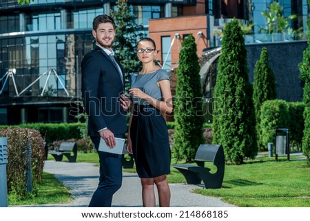 The best workers. Smiling businessman and successful businesswoman in formal clothes standing on the street and discuss business matters. Young businessman holding a tablet and looking into the camera