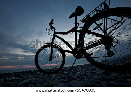 The bicycle against a sea landscape, costs on a pebble and a background of the sky after a sunset