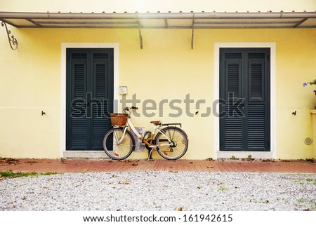 the bicycle parked near the house - stock photo
