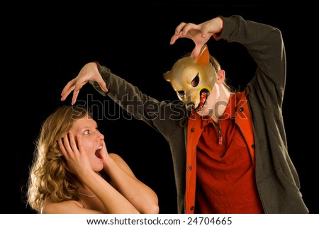 the big bad wolf and scared woman on the black background - stock photo