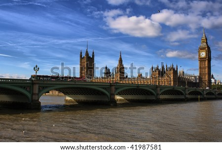 The Big Ben,the Houses of Parliament and Westminster bridge in London in a clear day with a dramatic looking sky