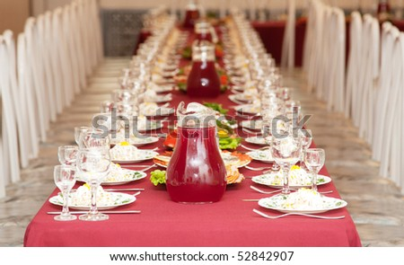 The big celebratory served table with dishes and a red cloth - stock photo