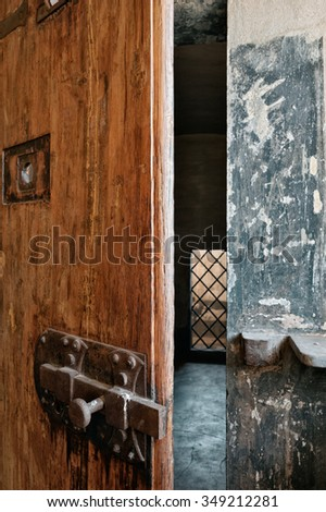 The big deadbolt on the wooden door of the prison cell - stock photo