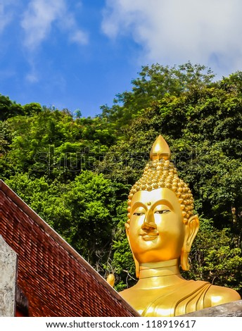 The big golden Buddha statue on hill on roof's church window