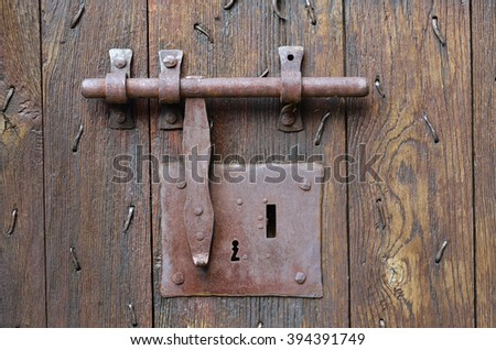 The Big Metal Lock With A Latch On The Wooden Surface Of The Ancient Batten  Door