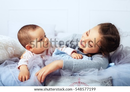 The big sister is in bed with the infant. The concept of family and lifestyle.