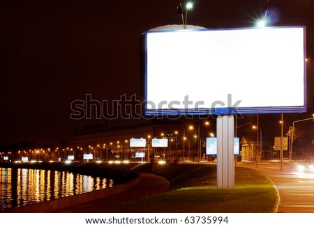The big white bill-board on night quay - stock photo